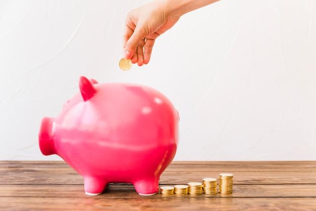 Menselijke hand munt invoegen in roze spaarpot Gratis Foto