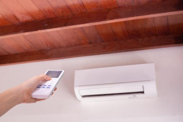 Menselijke hand te drukken op de afstandsbediening voor inschakelen airconditioner. Premium Foto