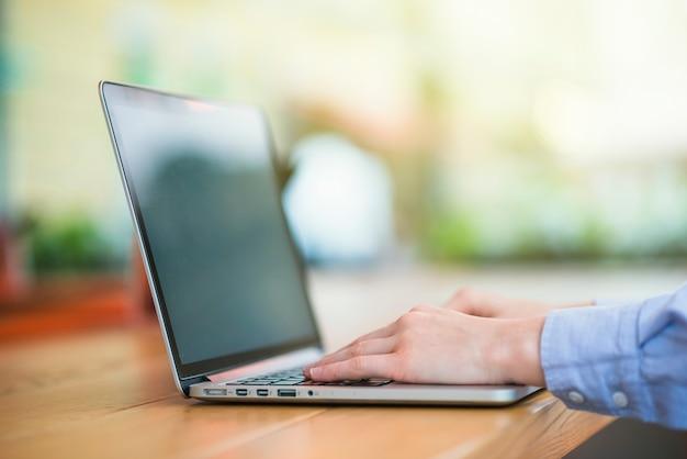Menselijke hand typen op laptop toetsenbord Gratis Foto