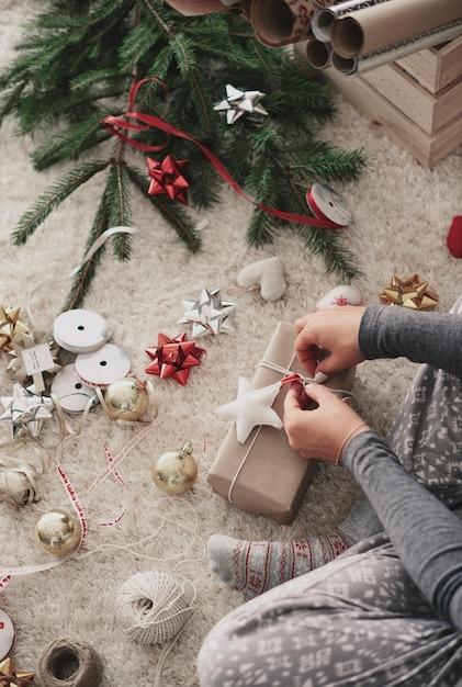 Menselijke hand voorbereiden van geschenken met kerstmis Gratis Foto