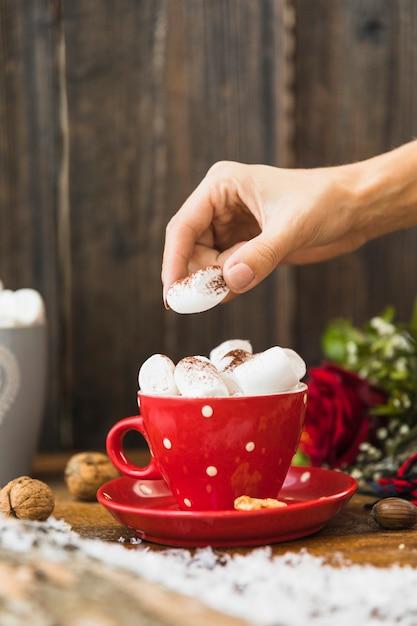 Menselijke hand zetten marshmallow in cup Gratis Foto
