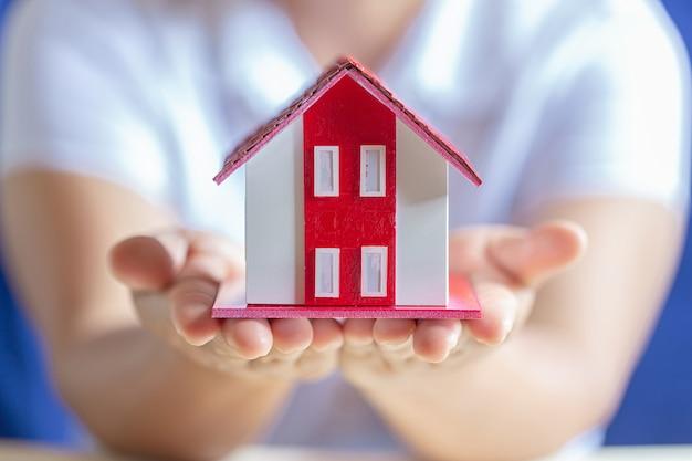 Menselijke handen die model van droomhuis houden Gratis Foto