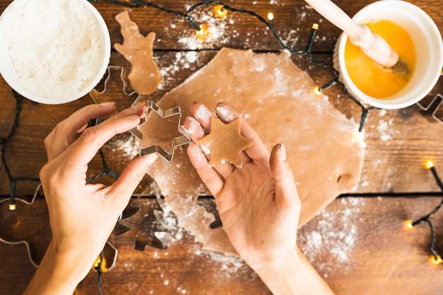 Menselijke handen die vorm voor koekje en deeg houden Gratis Foto