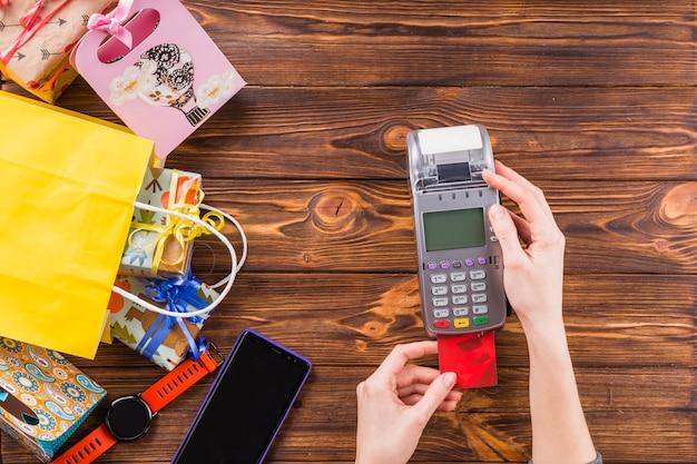 Menselijke handen met creditcard swipen machine voor betaling in de winkel Gratis Foto