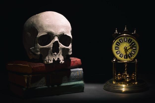 Menselijke schedel op oude boeken in de buurt van retro vintage klok op zwarte achtergrond onder lichtstraal. Premium Foto