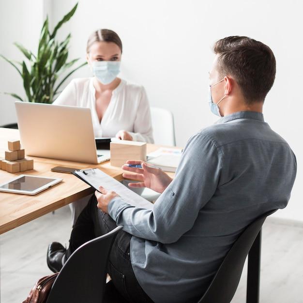 Mensen aan het werk op kantoor tijdens pandemie die medische maskers dragen Gratis Foto