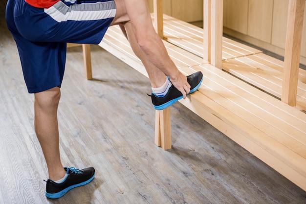 Mensen bindende schoenveter in kleedkamer bij de gymnastiek Premium Foto