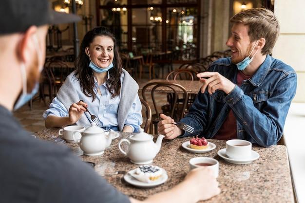 Mensen chatten in het restaurant met gezichtsmaskers Gratis Foto