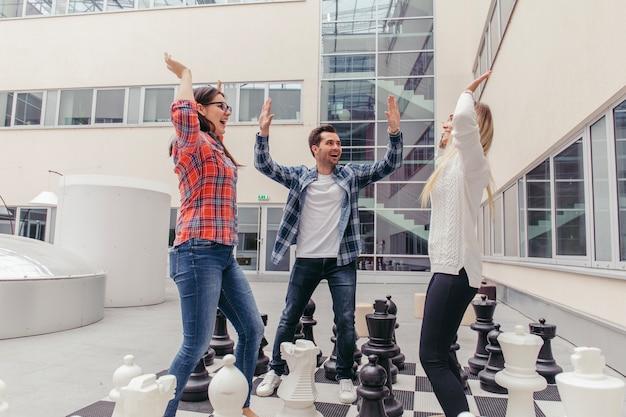 Mensen chillen op schaakbord Gratis Foto