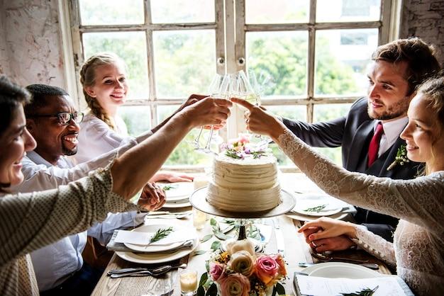 Mensen cling wijnglazen op huwelijksreceptie met bruid en bruidegom Gratis Foto