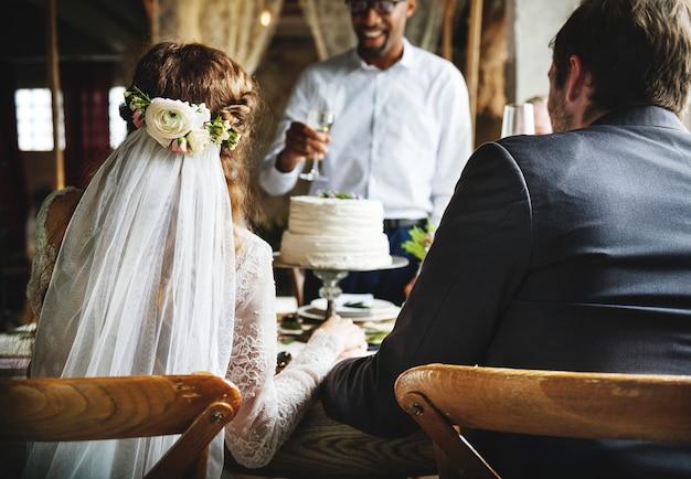 Mensen cling wijnglazen op huwelijksreceptie met bruid en bruidegom Premium Foto