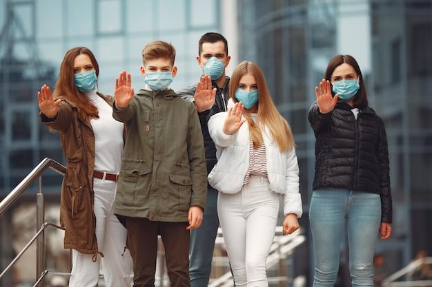 Mensen die beschermende maskers dragen, tonen stopbord door handen Gratis Foto