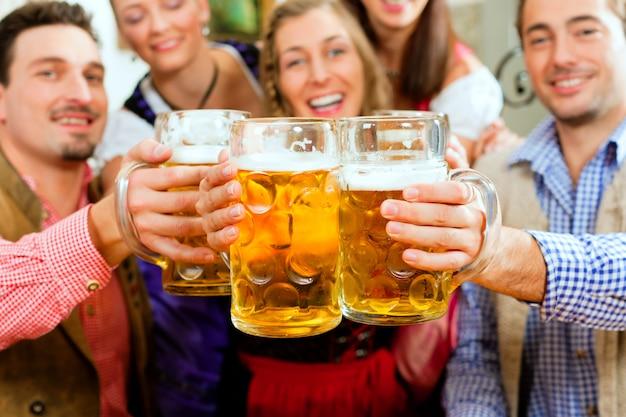 Mensen die bier drinken in beierse pub Premium Foto