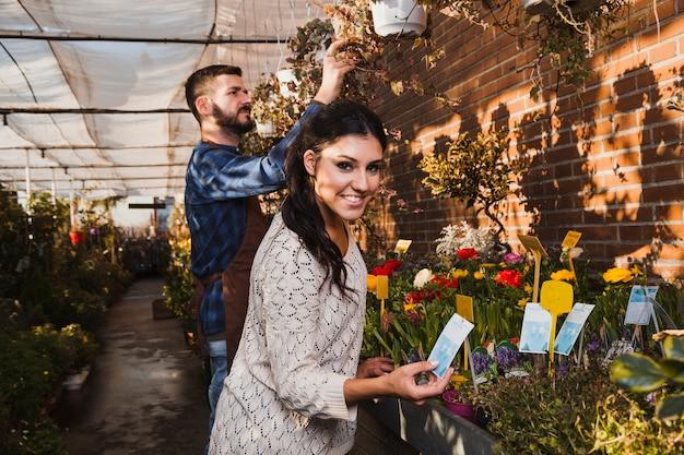 Mensen die bloemen in serre behandelen Gratis Foto