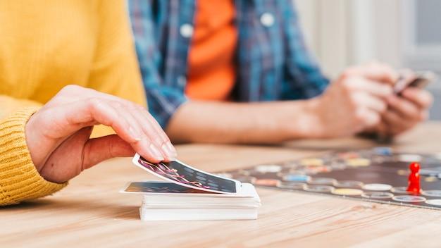 Mensen die een bedrijfsraadsspel op een houten bureau spelen Gratis Foto