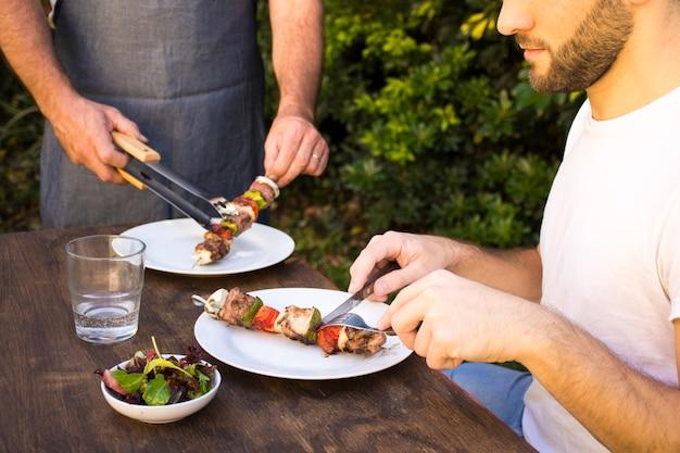Mensen die gekookte barbecue in platen op lijst proeven Gratis Foto
