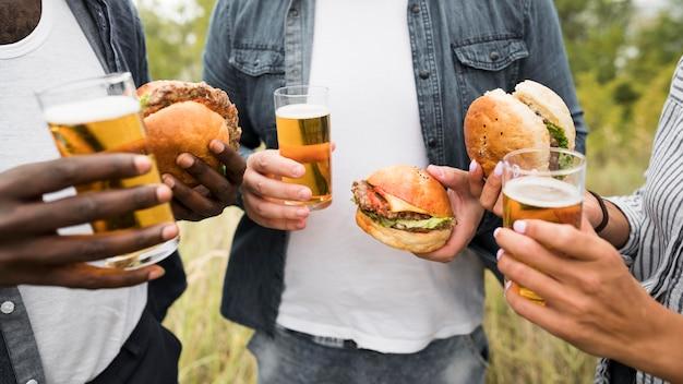Mensen die hamburgers houden Gratis Foto