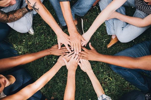Mensen die handen samen in het park stapelen Gratis Foto