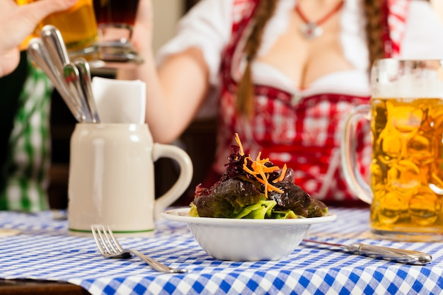 Mensen die in traditionele beierse tracht in restaurant of bar eten Premium Foto