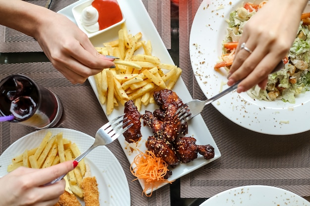 Mensen die kippenvleugels eten met bbq-saus en frietjes Gratis Foto