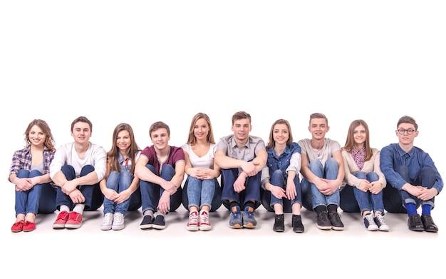 Mensen die op de vloer samen op wit zitten Premium Foto