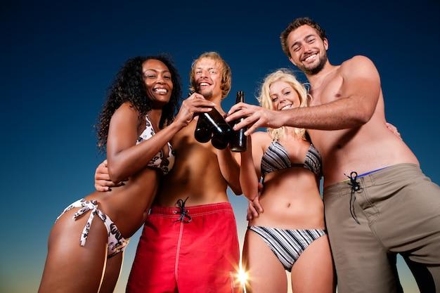 Mensen die partij hebben op strand met drankjes Premium Foto
