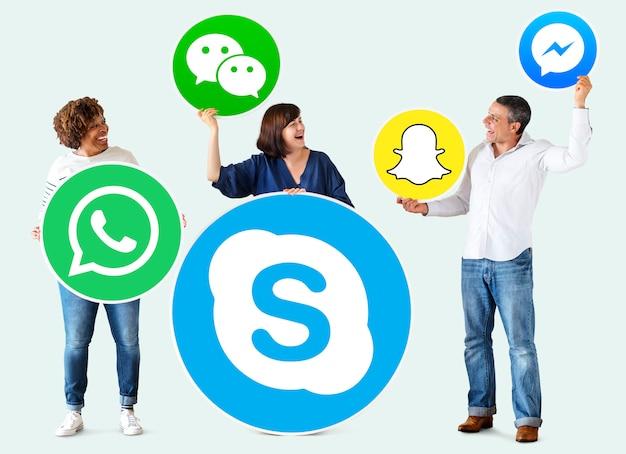 Mensen die pictogrammen van digitale merken houden Gratis Foto