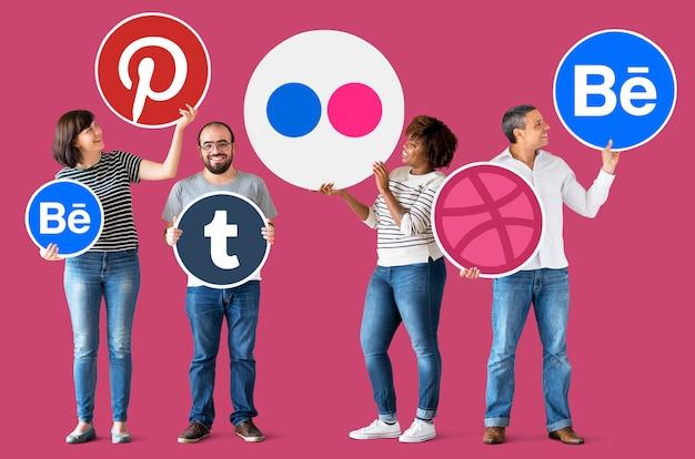 Mensen die pictogrammen van digitale merken houden Premium Foto