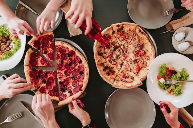 Mensen die pizza in een restaurant eten Gratis Foto