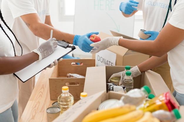 Mensen die samen vrijwilligerswerk doen in een donatiefaciliteit Gratis Foto