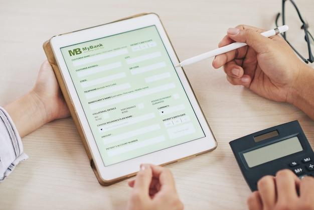 Mensen die tablet met bank-app gebruiken Gratis Foto