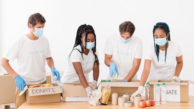 Mensen die verschillende pakketten met donaties voorbereiden Premium Foto