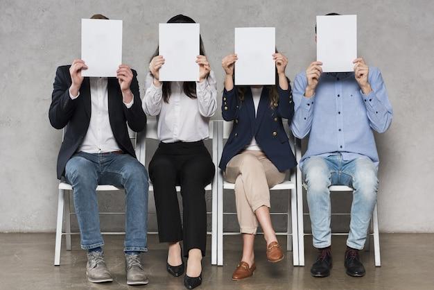 Mensen die wachten op hun sollicitatiegesprekken met blanco papieren Premium Foto