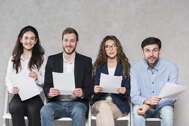 Mensen die wachten op hun sollicitatiegesprekken met cv's Premium Foto