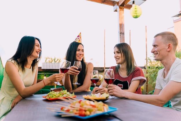 Mensen die wijn drinken en eten op verjaardagsfeestje Gratis Foto