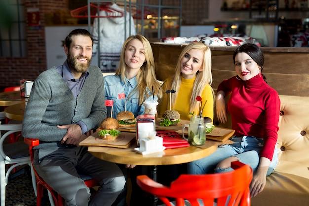 Mensen dineren samen aan een tafel in een café. happy vrienden eten hamburgers en drinken cocktails in het restaurant Premium Foto