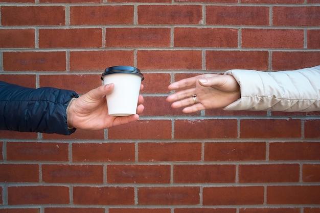 Mensen, dranken en zorgconcept - sluit omhoog van mannelijke en vrouwelijke hand die een kop van koffie van een mens nemen Premium Foto