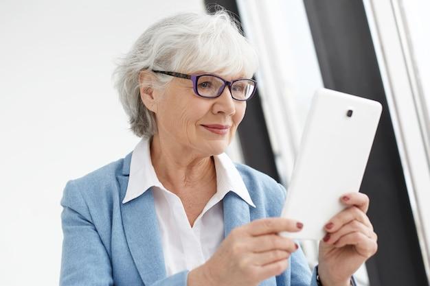 Mensen, elektronische gadgets, technologie en communicatieconcept. moderne slimme volwassen senior vrouw ondernemer in stijlvol pak en rechthoekige bril met digitale tablet, surfen op internet Gratis Foto