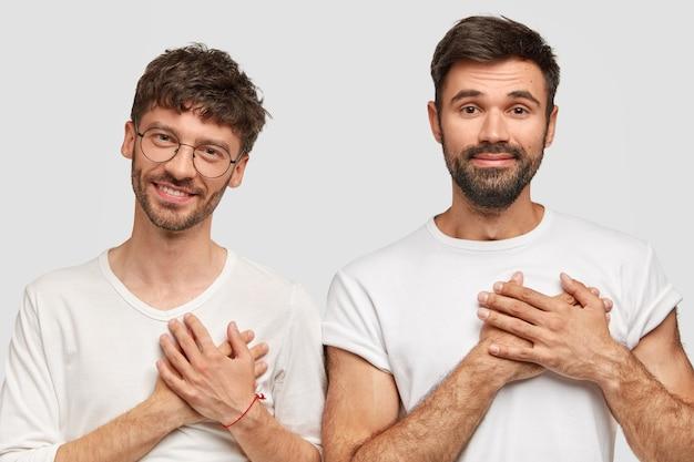 Mensen en dankbaarheid concept. dankbare tweemansstudenten die graag goede cijfers halen voor het examen, baard en snor hebben, gekleed in een casual wit t-shirt Gratis Foto