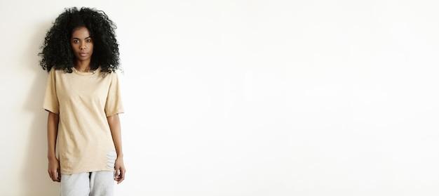Mensen en levensstijl concept. mooie jonge donkere vrouw, nonchalant gekleed met rust binnenshuis, staande bij lege witte muur en kijkt met een ernstige uitdrukking op haar gezicht Gratis Foto