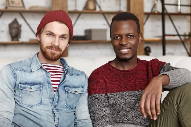 Mensen en levensstijl concept. twee gelukkige jonge mannen van verschillende etnische groepen samen tijd doorbrengen, zittend op de bank dicht bij elkaar. stijlvolle witte man in hoed binnenshuis rusten met zijn zwarte vriend Gratis Foto
