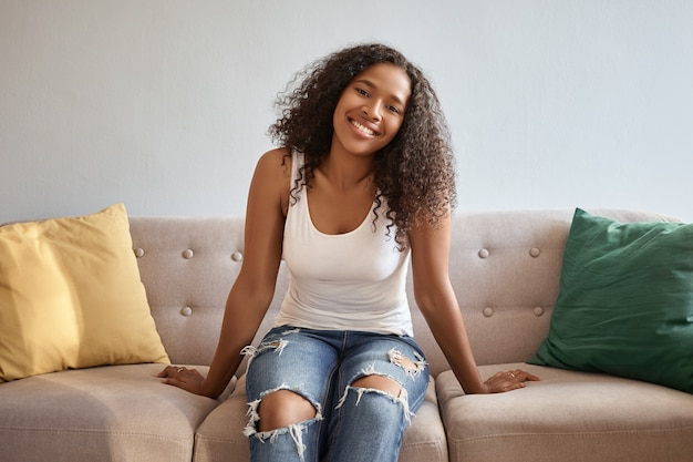Mensen en levensstijl. mooie jonge donkere vrouw in blauwe gescheurde spijkerbroek en witte tank top ontspannen thuis, zittend op comfortabele grijze bank met kussens, breed glimlachend Gratis Foto