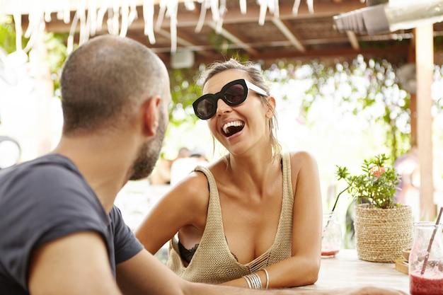 Mensen en levensstijlconcept. buiten schot van vrouw in stijlvolle tinten lachen om grappen van bebaarde man tijdens date, ontspannen in café op zonnige dag. Gratis Foto