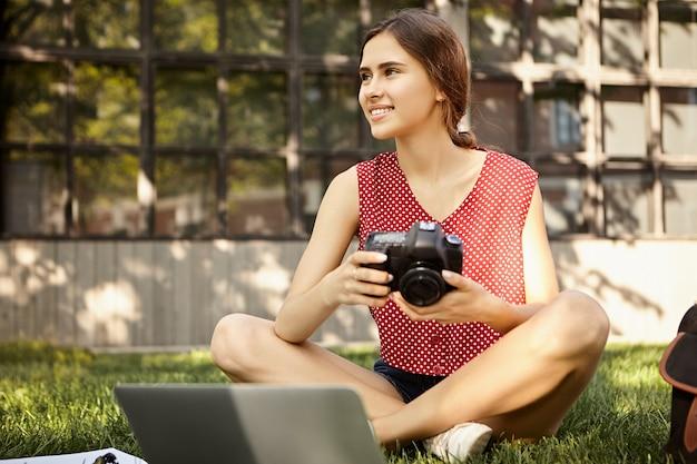 Mensen en levensstijlconcept. foto van professionele vrouwelijke fotograaf in stijlvolle kleding met dslr camera zittend op het gras voor draagbare computer, foto's van zomer foto-opnamen retoucheren Gratis Foto