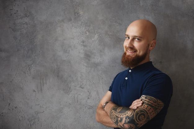Mensen en levensstijlconcept. knappe zelfverzekerde jonge bebaarde europese man met sluwe glimlach, armen gekruist op zijn borst, staande aan de muur met copyspace voor uw promotionele inhoud Gratis Foto