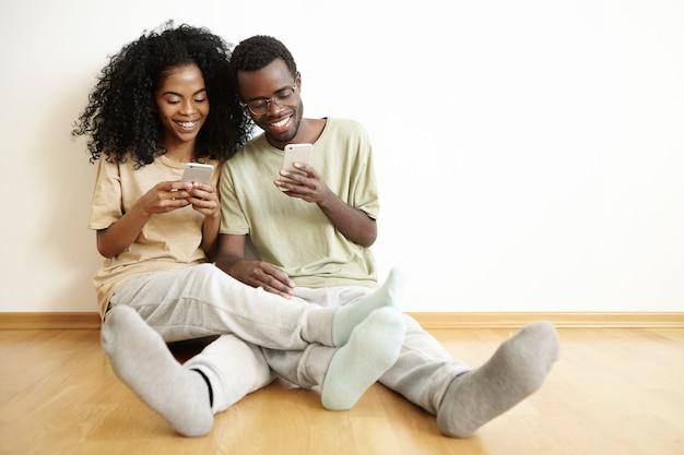 Mensen en moderne technologie. casual gezellige afrikaanse paar tijd samen doorbrengen met online winkelen of apps op gadgets gebruiken, genieten van gratis wi-fi thuis, zittend op de vloer Gratis Foto