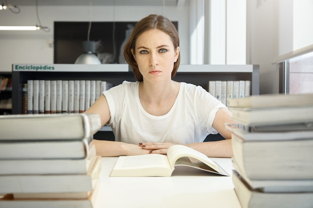 Mensen en onderwijsconcept. moe vrouwelijke student studeert, leest leerboek over economie, bereidt zich voor op mba-test of examen, voelt zich uitgeput, zit aan bureau in bibliotheek Gratis Foto