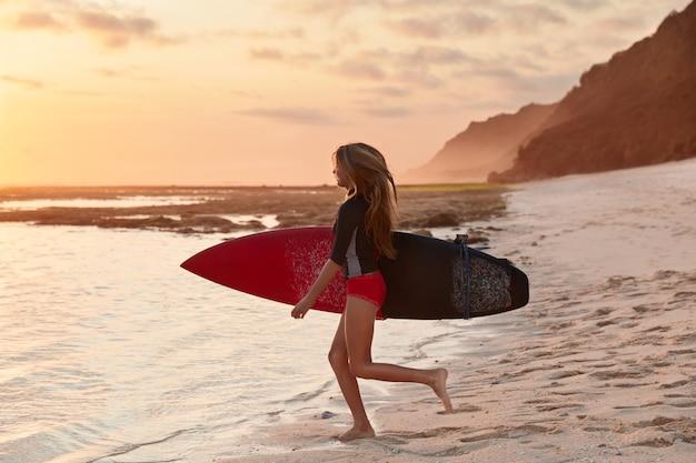 Mensen en reisconcept. schot van slanke surfer met perfect figuur Gratis Foto
