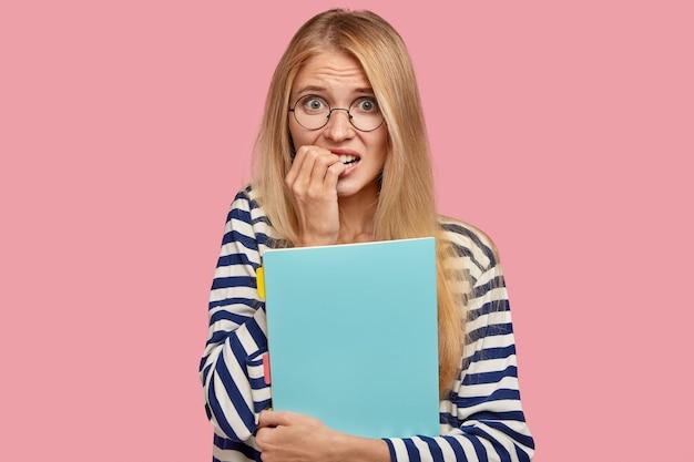 Mensen en universitair leven concept. nerveus bezorgd aangenaam uitziende student bijt vingernagels van zenuwen Gratis Foto