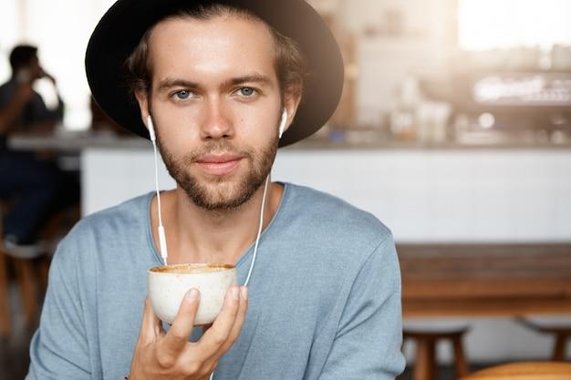 Mensen en vrije tijd concept. headshot van aantrekkelijke jonge hipster in trendy zwarte hoed koffie drinken en muziek luisteren Gratis Foto